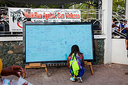 Runner Valerie Washington signs the message board in Emancipation Garden.  Virgin Islanders gear up for the 2-mile Virgin Islands Walk/Run Against Gun Violence along the Charlotte Amalie Waterfront.   Proceeds from the event go to benefit the Jason Carroll Memorial Fund for college scholarships.  St. Thomas, VI.  22 May 2016.  © Aisha-Zakiya Boyd