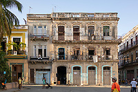 A beautiful old building with people, and a dog, looking at something off camera  in a city square in Old Havana.