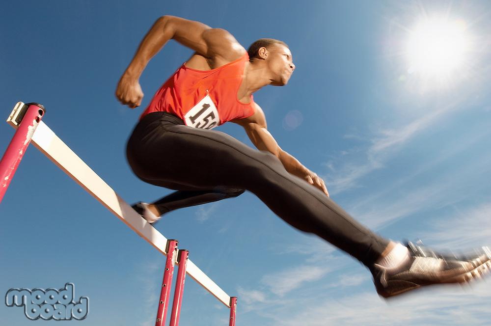 Male athlete jumping hurdle mid air