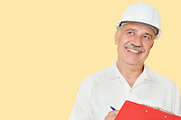 Senior constructor with clipboard looking away over yellow background
