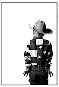 "SHOT 1/22/2003 - Four year-old Joshua Walker of Westminster, Co. sticks his thumbs into his pint-sized Wranglers while posing for a portrait recently at the National Western Stock Show and Rodeo. Walker was there with his sister and parents, who said that Grandma dresses them when they go to the National Western. Walker and his sister were hoping to participate in the mutton busting event at the Rodeo. The National Western Stock Show is held every January at the National Western Complex in Denver, Colorado. First held in 1906, it is the world's largest stock show by number of animals and offers the world?s only carload and pen cattle show in the historic Denver Union Stockyards. The stock show is governed by the Western Stock Show Association, a Colorado 501 (c) 3 institution, which produces the annual National Western Stock Show in an effort to forward the association's mission: ""To preserve the western lifestyle by providing a showcase for the agricultural industry through emphasis on education, genetic development, innovative technology and offering the world's largest agricultural marketing opportunities."" Proceeds from the National Western Stock Show go to the National Western Scholarship Trust. The Trust awards 64 scholarships annually to students studying agriculture and medicine to practice in rural areas at colleges and universities in Colorado and Wyoming..(Photo by Marc Piscotty / © 2003)"