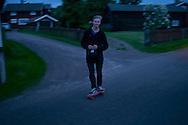Young man riding a pink skateboard at night. Västanvik, Sweden