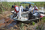 July 10, 2010, Members of Plaquemines Parish Inland Waterway Strike force,  cleaning up oil in Jackass Bay with a shop vac sucking the oil off the surface of the water. The Inland Waterway Strike Force of Plaquemines Parish set up by Billy Nungesser to cleanup and contain the BP oil as it gets into the marsh joined  clean up crews set up by BPs private contractors.