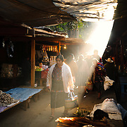 A woman walks through the covered stalls of Chichi's Sunday market with sun streaming through. Chichicastenango is an indigenous Maya town in the Guatemalan highlands about 90 miles northwest of Guatemala City and at an elevation of nearly 6,500 feet. It is most famous for its markets on Sundays and Thursdays.