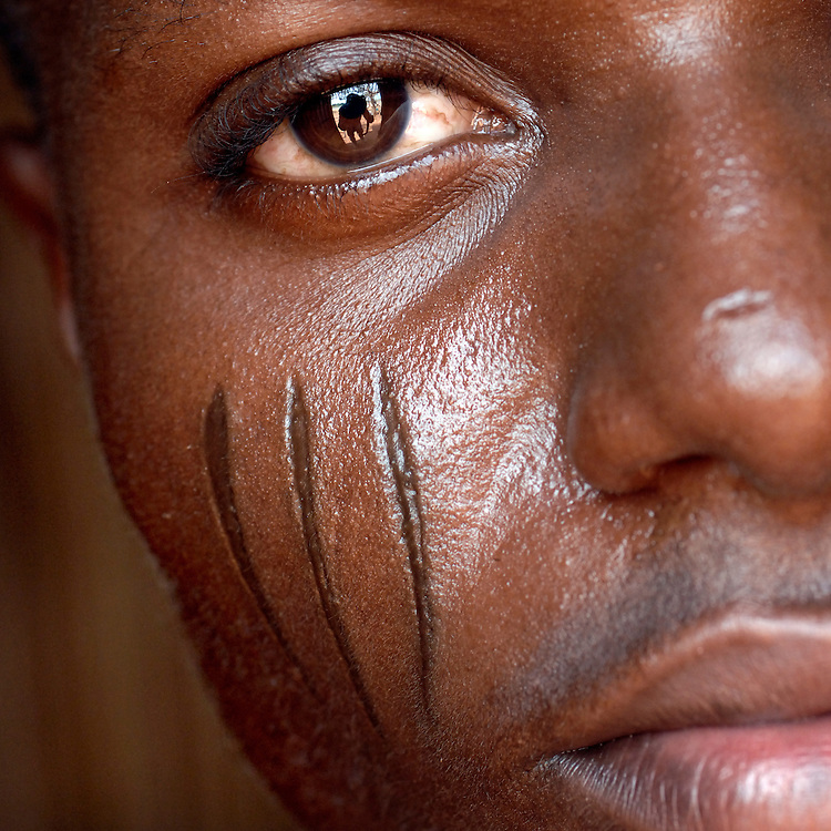 Benin, Abomey-Calavi December 02, 2006 - Man with tribal scarification on his face. Scarification is used as a form of initiation into adulthood, beauty and a sign of a village, tribe, and clan.
