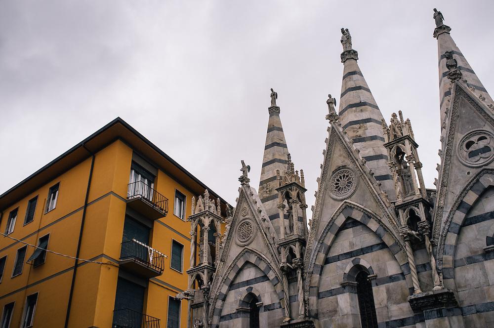 Santa Maria della Spina next to a colourful building in Pisa, Italy
