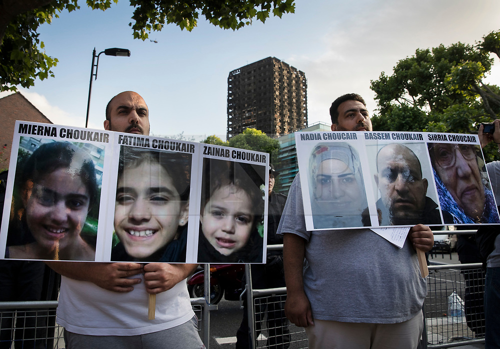 © Licensed to London News Pictures. 16/06/2017. London, UK. Relatives hold photographs of missing family members in  sight of Grenfell Tower as marchers arrive from a protest at Kensington Town Hall. Demonstrators calling for justice for victims of the fire had earlier briefly occupied part of Kensington and Chelsea Town Hall. The blaze engulfed the 27-storey building in the early hours of June 13th. Police say 30 people have been killed with 34 still in hospital, 18 of whom are in critical condition. The fire brigade say that they don't expect to find anyone else alive. Photo credit: Peter Macdiarmid/LNP