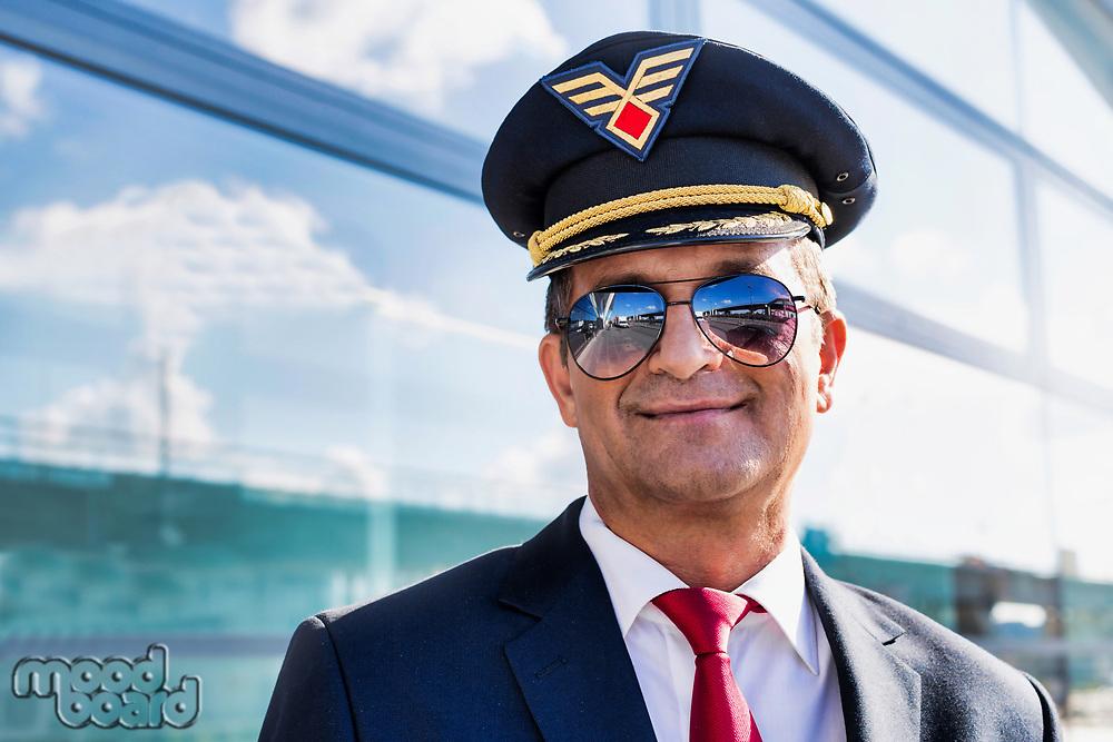 Portrait of mature confident pilot captain  wearing eyeglasses in airport