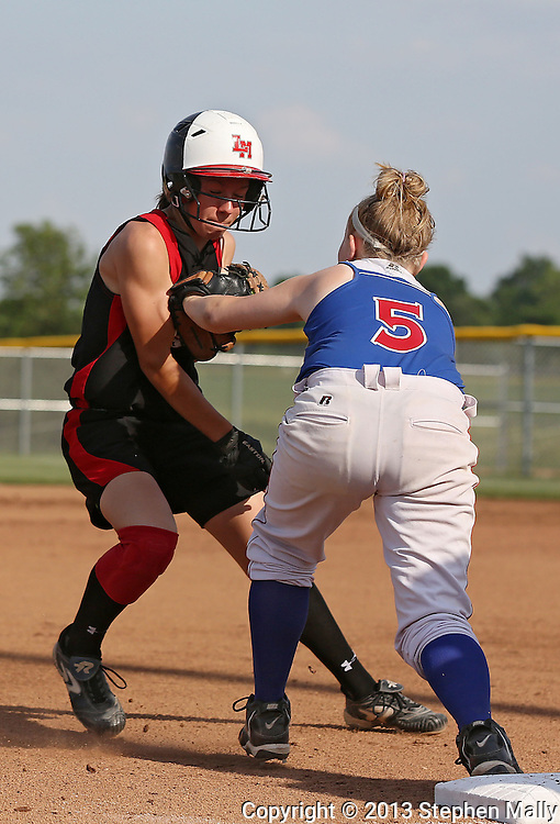 Linn-Mar's Elison Ollinger (8) is tagged out while trying to make it to third base by Washington's Anne Riley (5) during the softball game between Cedar Rapids Washington and Linn-Mar at Oak Ridge Middle School in Marion on Thursday, June 20, 2013. The Lions defeated the Warriors 7-6 in 9 innings.