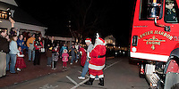 Santa Claus arrives at Heath's Supermarket in Center Harbor in grand style on Engine #4 Friday evening much to delight of dozens of children and their families awaiting his visit.   (Karen Bobotas/for the Laconia Daily Sun)