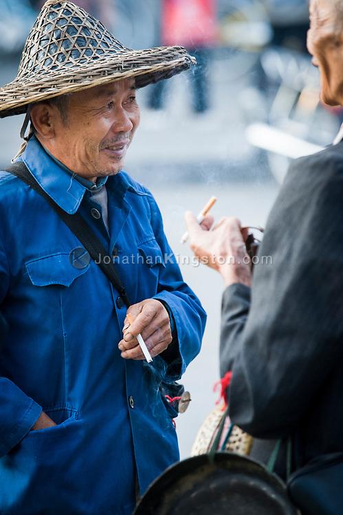 Man wearing an Asian style hat smoking a cigarette in Yangshuo, China.