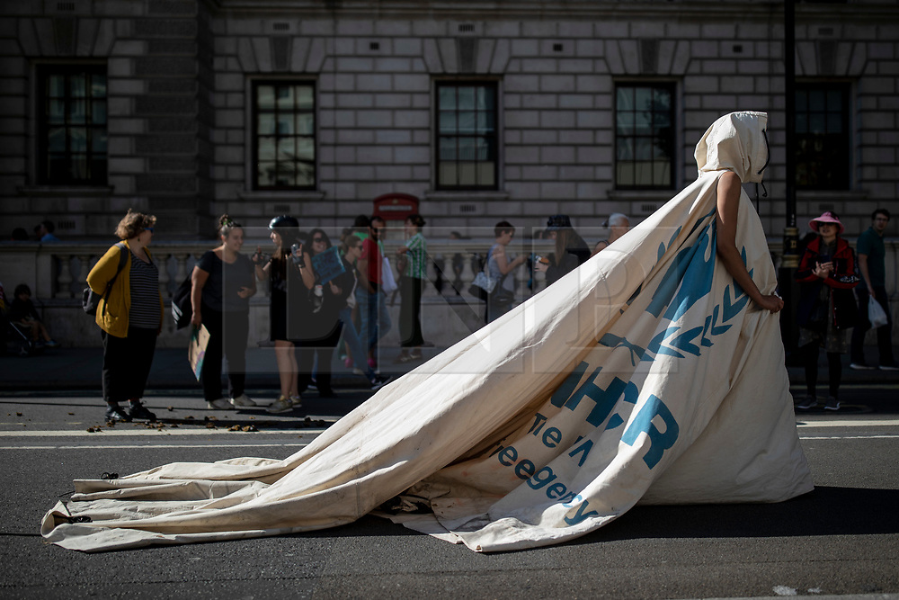 © Licensed to London News Pictures. 20/09/2019. London, UK. A performer wearing 'Dress for Our Time' by artist and designer Helen Storey walks down Whitehall in London as tens of thousands join the Global Climate Strike in London. Protests about the climate crisis are being led by young people in cities around the world, with millions expected to attend. Photo credit: Rob Pinney/LNP