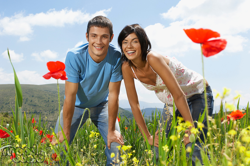Young couple standing in mountain meadow portrait front view