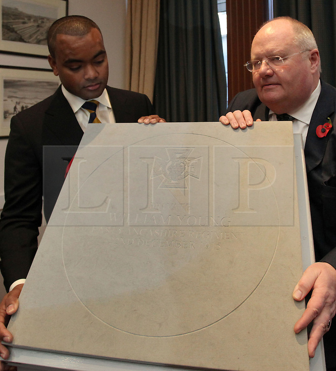 © Licenced to London News Pictures. 04/11/2013. London. UK.  <br /> Communities Secretary Eric Pickles (right) and Lance Sergeant Johnson Beharry (left), the first living recipient of the Victoria Cross in over 30 years, unveil the design of the paving stone which will commemorate recipients of the Victoria Cross during the First World War at the Army and Navy Club in London, November 4th 2013. The winning design, following a national competition, will be set in stone in over 400 communities across the United Kingdom to commemorate those First World War soldiers who were awarded the Victoria Cross for valour 'in the face of the enemy'.<br /> Photo Credit: Susannah Ireland