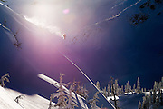 A backlit lens flare photo of local professional snowboarder Rusty Ockenden as he hits a stepdown snowboard jump on Face Mountain near Pemberton British Columbia near Whistler