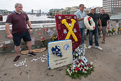 June 24, 2017 - London, United Kingdom -  Supporters pose with wreaths on London Bridge after the march by well over a thousand supporters of the recently formed Football Lads Alliance marched to the centre of London Bridge to protest what they see as the UK government's reluctance in tackling the current extremism problem. They marched in silence and without banners, posters or placards to a short rally and moment of silence. Police had imposed conditions on the event under Section 12 and 14 of the Public Order Act, 1986, due to concerns of serious public disorder, and disruption to the community, which prevented them from marching to Borough Market.  Peter Marshall ImagesLive (Credit Image: © Peter Marshall/ImagesLive via ZUMA Wire)
