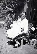 grandmother holding newborn baby sitting in the garden France