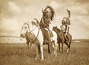 Three Native American chiefs mounted on horses and wearing feather headdresses.  Photograph c1890.
