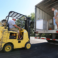 Thomas Wells | Buy at PHOTOS.DJOURNAL.COM<br /> Tim Spann, left, unloads the first pallet of furniture for the new Tupelo Police Headquarters Monday.