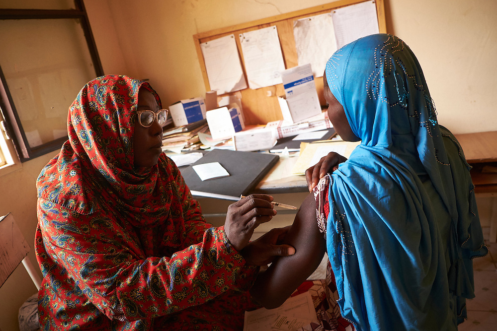 Medical assistant Yayé Aissa Boubacar administers a tetanus injection to Amadou Saâotatou, 18 years old, 5 months pregnant  at the Saguia health centre, Niamey, Niger on February 16, 2016. The Saguia Health Centre serves a population of 9353 people thanks to a team of 20 people including 3 nurses and 4 midwives who receive pregnant women for prenatal consultations from Monday to Friday. During the first prenatal consultation the pregnant women receive a first dose of vaccinations and a booster on their second consultation. The third, fourth and fifth doses are administered later. This vaccination reinforces the immunity of the mothers and their children. The vaccination for against tetanus is free for pregnant women children under 5 years of age. To reach the population whom do not frequent health centres the district health department organise consultations in villages once per month that are more than 15km from the health centre.
