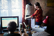 Yaroslav, 10, is using the computer while his mother Olga, 36, is showing some of the clothes she also knits to earn living, while inside the provisional home where they live as internally displaced persons. (IDPs) Yeroslav is taking part to the UNICEF-sponsored One Minute Junior project for internally displaced persons (IDPs), carried out by the local NGO 'Ukrainian Frontiers' in the city of Kharkiv, the country's second-largest, in the east. The conflict between Ukrainian army and Russia-backed separatists nearby, in the Donbass region, have left more than 10000 dead since April 2014, including over 1000 since the shaky Minsk II ceasefire came into effect in February 2015. The approximate number of people displaced by the conflict is 1.4 million as of August 2015. Yeroslav's mother, Olga, is also a participant to a different project of 'Ukrainian Frontiers', called 'Self-Employment', first as a beneficiary, and now as a paid hotline coordinator for people seeking jobs and formation courses.