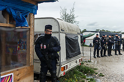 October 18, 2016 - Calais, France - Police stands during a police operation in the Calais Jungle, on October 18, 2016. The refugee camp on the coast to the English Channel is to be cleared in the next few days, according to the French government. In the camp live around the 1000 refugees and wait for the possibility to travel further through the Eurotunnel to the UK. (Credit Image: © Markus Heine/NurPhoto via ZUMA Press)