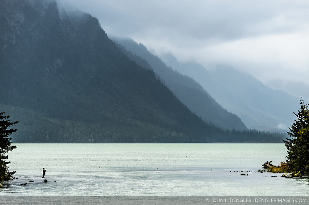 A lone fisherman fishes at the outlet of Chilkoot Lake at the Chilkoot Lake State Recreation Site near Haines, Alaska. <br /> <br /> The Chilkoot River outlet of Chilkoot Lake offers some of the best salmon fishing in Southeast Alaska. Four salmon runs are an open invitation for bears to feast on the spawning salmon. At times, the Chilkoot River Corridor has some of the highest bear activity in the state. The Chilkoot River corridor area is extremely narrow with room for an equally narrow road with few pullouts for tourists and fisherman causing traffic and congestion. This creates a serious conflict between humans and bears.<br /> <br /> The Chilkoot River ranks second in popularity for Southeast Alaska freshwater sports fishing. The area is also an important cultural area for the Tlingit people and site of a culture camp.