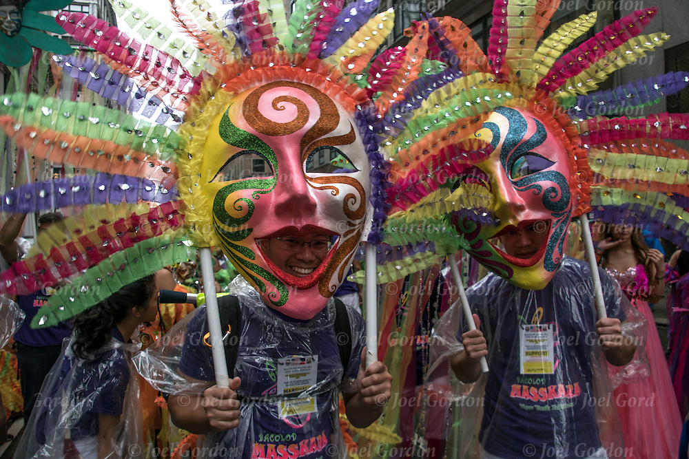 "Looking into the camera wearing traditional ""Masskara"" masks.  They are just a few of  the many faces in the Philippine Independence Day Parade in NYC."
