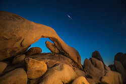 Nightt sky and stars on arch at White Tank, Joshua Tree National Park, California, USA.