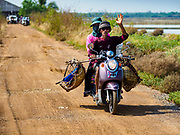 20 FEBRUARY 2019 - BAN LAEM, PHETCHABURI, THAILAND: Salt workers leave the fields on their motorcycle after finishing on one of the first days of the 2019 salt harvest in Ban Laem, Thailand. Ban Laem's salt fields are expanding because salt harvesters in Samut Sakhon and Samut Songkhram,  which are closer to Bangkok, are moving to Ban Laem as their land is turned into industrial parks.    PHOTO BY JACK KURTZ