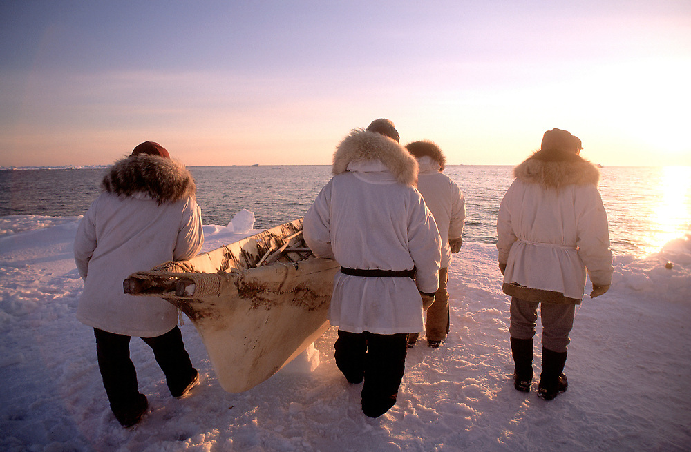 Sunset over a native whaling crew and their umiak on the frozen sea ice near Barrow, Alaska