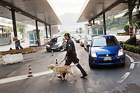 COMO, ITALY - 25 October 2013: A Dog Unit of the Guardia di Finanza (Financial Police) walks with its cash dog towards a car suspected of carrying undeclared cash into Switzerland for an inspection in Como, Italy, at the border with Chiasso (Switzerland) on October 25th 2013. Cash dogs are sniffer dogs that have specially trained to detect the ink on currency notes. In the effort of cracking down on tax evasion and cash smuggling, the Guardia di Finanza works with highly trained dogs in outposts along its borders with Switzerland and France, and in international airports such as Rome Fiumicino and Milano Malpensa.<br /> <br /> In Italy, the law allows to travel with up to 10,000 euros in cash. Beyond that, one must declare to the authorities.<br /> <br /> In 2012, the Guardia di Finanza of the  borders with Chiasso in Switzerland have intercepted more than 55 million euros not declared. In 2013, until September 31st, they have intercepted more than 92 million euros.  The Guardia di Finanza of the Chiasso outpost has been using cash dogs since 2010.