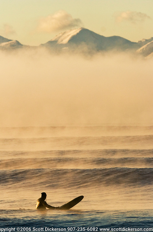 Ty Gates prepares to catch a  wave on a cold foggy morning of winter surf beneath snow covered mountains in Homer, Alaska, USA.