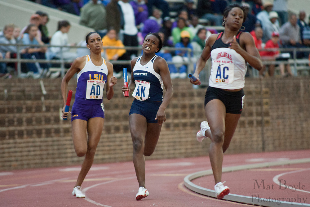 Runners round the turn during heats of the college women's 4x400.