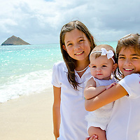 Sisters Leilani and Ke'alohi taking care of their baby sister Emma on the beach