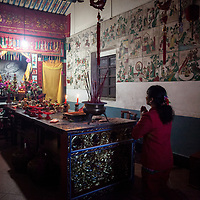 A woman, wearing auspicious red, prays at the altar of a Mazu temple. <br />
