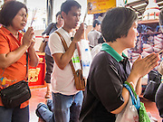 "26 AUGUST 2013 - BANGKOK, THAILAND: People pray after donating food to the Poh Teck Tung Foundation for Hungry Ghost Month in Bangkok. Poh Teck Tung operates hospitals and schools and provides assistance to the poor in Thailand. The seventh lunar month (August - September in 2013) is when the Chinese community believes that hell's gate will open to allow spirits to roam freely in the human world for a month. Many households and temples will hold prayer ceremonies throughout the month-long Hungry Ghost Festival (Phor Thor) to appease the spirits. During the festival, believers will also worship the Tai Su Yeah (King of Hades) in the form of paper effigies which will be ""sent back"" to hell after the effigies are burnt.     PHOTO BY JACK KURTZ"