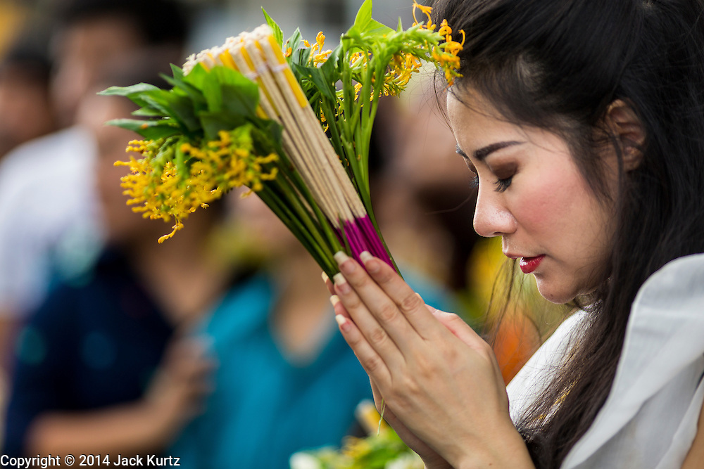 "12 JULY 2014 - PHRA PHUTTHABAT, SARABURI, THAILAND:  A woman prays before presenting a monk with flowers during the Tak Bat Dok Mai at Wat Phra Phutthabat in Saraburi province of Thailand. Wat Phra Phutthabat is famous for the way it marks the beginning of Vassa, the three-month annual retreat observed by Theravada monks and nuns. The temple is highly revered in Thailand because it houses a footstep of the Buddha. On the first day of Vassa (or Buddhist Lent) people come to the temple to ""make merit"" and present the monks there with dancing lady ginger flowers, which only bloom in the weeks leading up Vassa. They also present monks with candles and wash their feet. During Vassa, monks and nuns remain inside monasteries and temple grounds, devoting their time to intensive meditation and study. Laypeople support the monks by bringing food, candles and other offerings to temples. Laypeople also often observe Vassa by giving up something, such as smoking or eating meat. For this reason, westerners sometimes call Vassa ""Buddhist Lent.""   PHOTO BY JACK KURTZ"