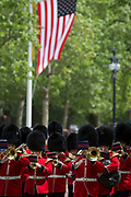 On US President Donald Trump's first day of a controversial three-day state visit to the UK by the 45th American President, a guards band marches down the Mall, beneath the US Stars and Stripes flag, on 3rd June 2019, in London England.