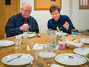 """26 FEBRUARY 2020 - FARMINGTON, MINNESOTA: GARY SMITH and DEE PARKER eat dinner at the community dinner at Faith Church, a United Methodist Church in Farmington, MN, about 30 minutes south of the Twin Cities. The dinner is sponsored by Loaves & Fishes, a Christian organization that provides food for community dinners and foodbanks. Farmington, with a population of 21,000, is a farming community that has become a Twin Cities suburb. The city lost its only grocery store, a Family Fresh Market, in December, 2019. Smith said he used to shop at the now closed several times a week but now he has drive much further to shop so doesn't shop as often. He also said he misses the community spirit the closed store, he and his friends used to meet there for coffee. The closing turned the town into a """"food desert."""" In January, Faith Church started serving the weekly meals as a response to the store's closing. About 125 people per week attend the meal at the church, which is just a few blocks from the closed grocery store. The USDA defines food deserts as having at least 33% or 500 people of a census tract's population in an urban area living 1 mile from a large grocery store or supermarket. Grocery chains Hy-Vee and Aldi both own land in Farmington but they have not said when they plan to build or open stores in the town.     PHOTO BY JACK KURTZ"""