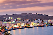 Dusk view of the Mutrah waterfront and the mountains surrounding Muscat, the capital of the Sultanate of Oman.