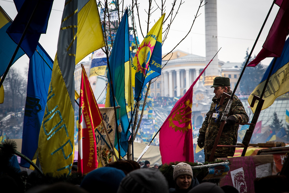 A man, dressed with military clothes, stands on a barricade above protesters, at the entrance of the Independace Square in Kiev.
