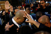 Religious leaders from all denominations lay hands on Mayor Cory Booker on the playground where three young  people were killed in 2007.