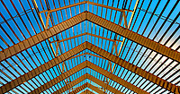 Metallic Mirror Image: The metal framework of a large horse barn takes on a golden colour in the mornings light and it makes a strong geometric, mirror image, Langley British Columbia, Canada.