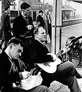 All Blacks on 1963-64 tour of Britain and France. From left: Dennis Young, unknown with ukelele and Wilson Whineray.<br /> Photosport