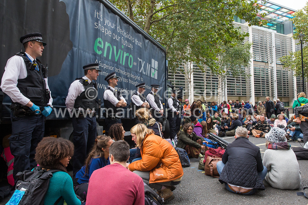 London, UK. 7 October, 2019. Metropolitan Police officers and climate activists from Extinction Rebellion surround a large truck blocking the road outside the Home Office on the first day of International Rebellion protests to demand a government declaration of a climate and ecological emergency, a commitment to halting biodiversity loss and net zero carbon emissions by 2025 and for the government to create and be led by the decisions of a Citizens' Assembly on climate and ecological justice.