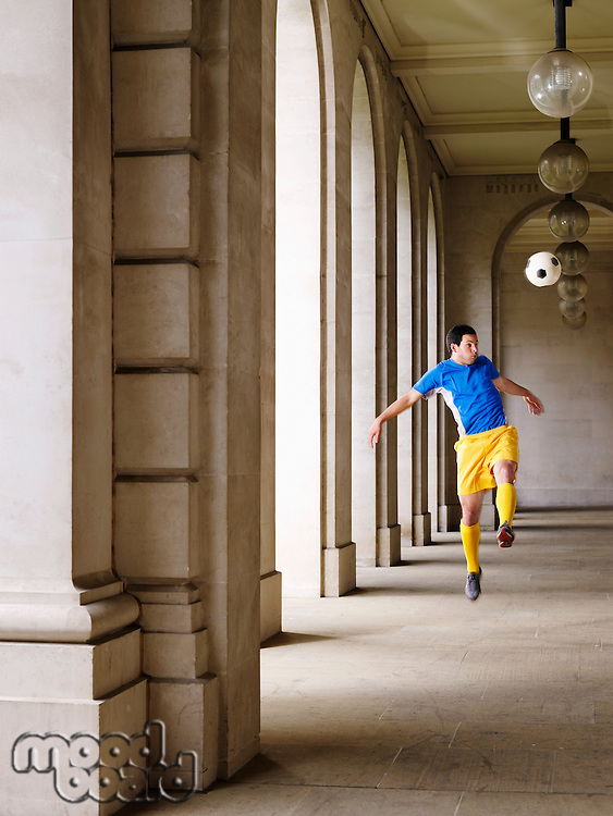 Soccer player kicking ball in portico
