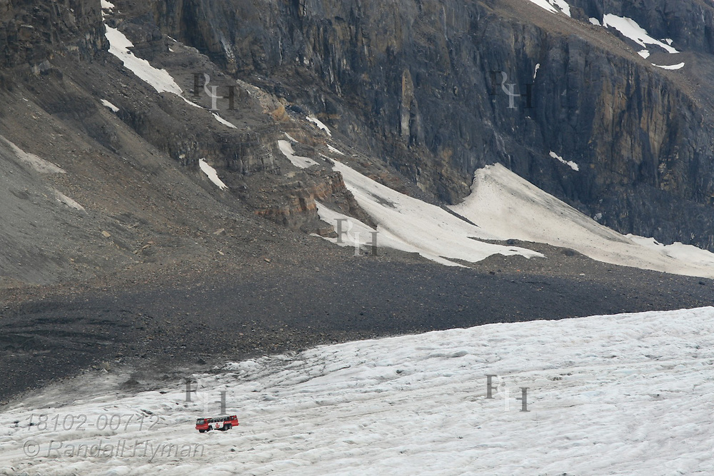 Huge all-terrain bus looks tiny amid ice and mountain wall at foot of Columbia Icefield in Jasper National Park, Alberta, Canada.