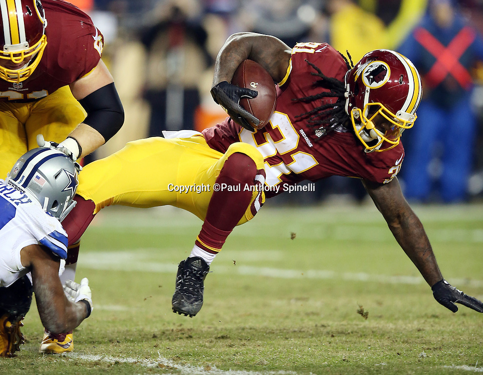 Washington Redskins running back Matt Jones (31) tries to keep his balance with an outstretched hand as he gets tackled while running the ball in the second quarter during the 2015 week 13 regular season NFL football game against the Dallas Cowboys on Monday, Dec. 7, 2015 in Landover, Md. The Cowboys won the game 19-16. (©Paul Anthony Spinelli)