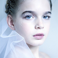 Young girl looking at camera with blue eyes and white veil